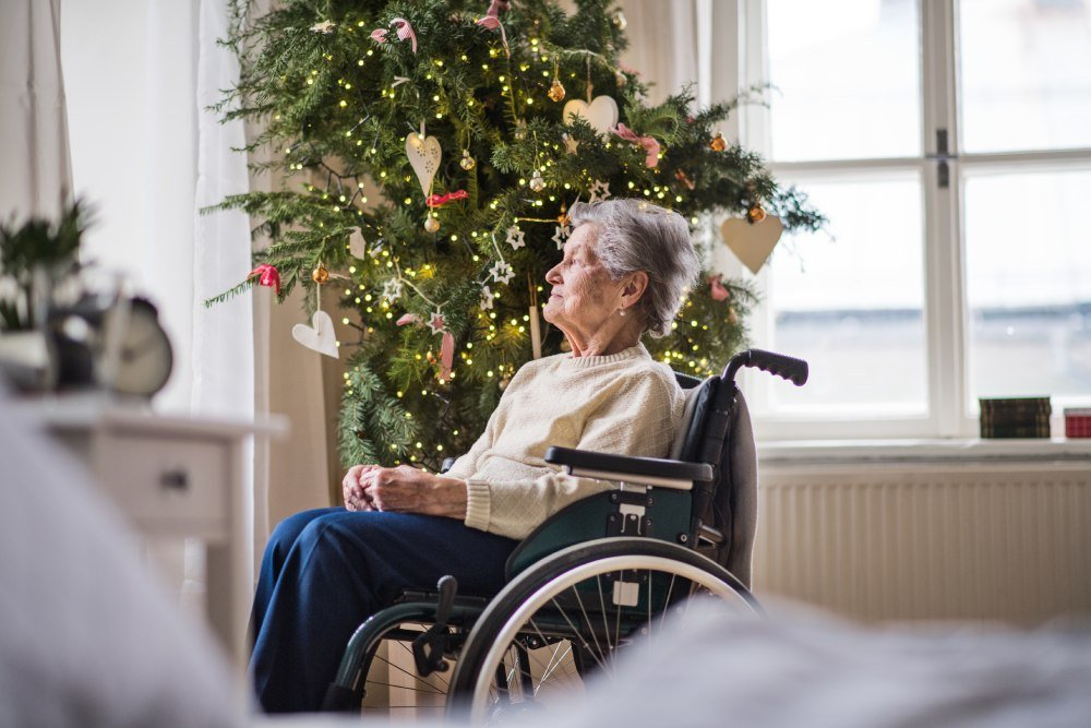 Elderly lady sat next to a christmas tree in a wheelchair